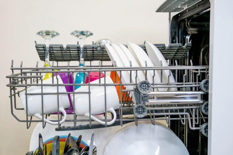 colorful Dishware inside built-in dishwasher, glasses, mugs, plates, wine glasses . Dishwashing machine rack