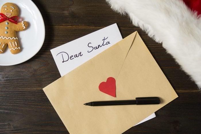 Letter for Santa in an envelope, pen. Gingerbread on background