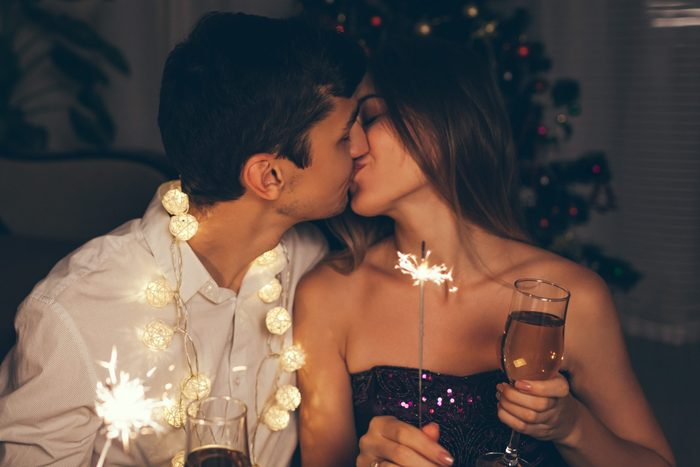 Christmas and New year party concept. Couple kissing, burning sparklers by illuminated Christmas tree with champagne.