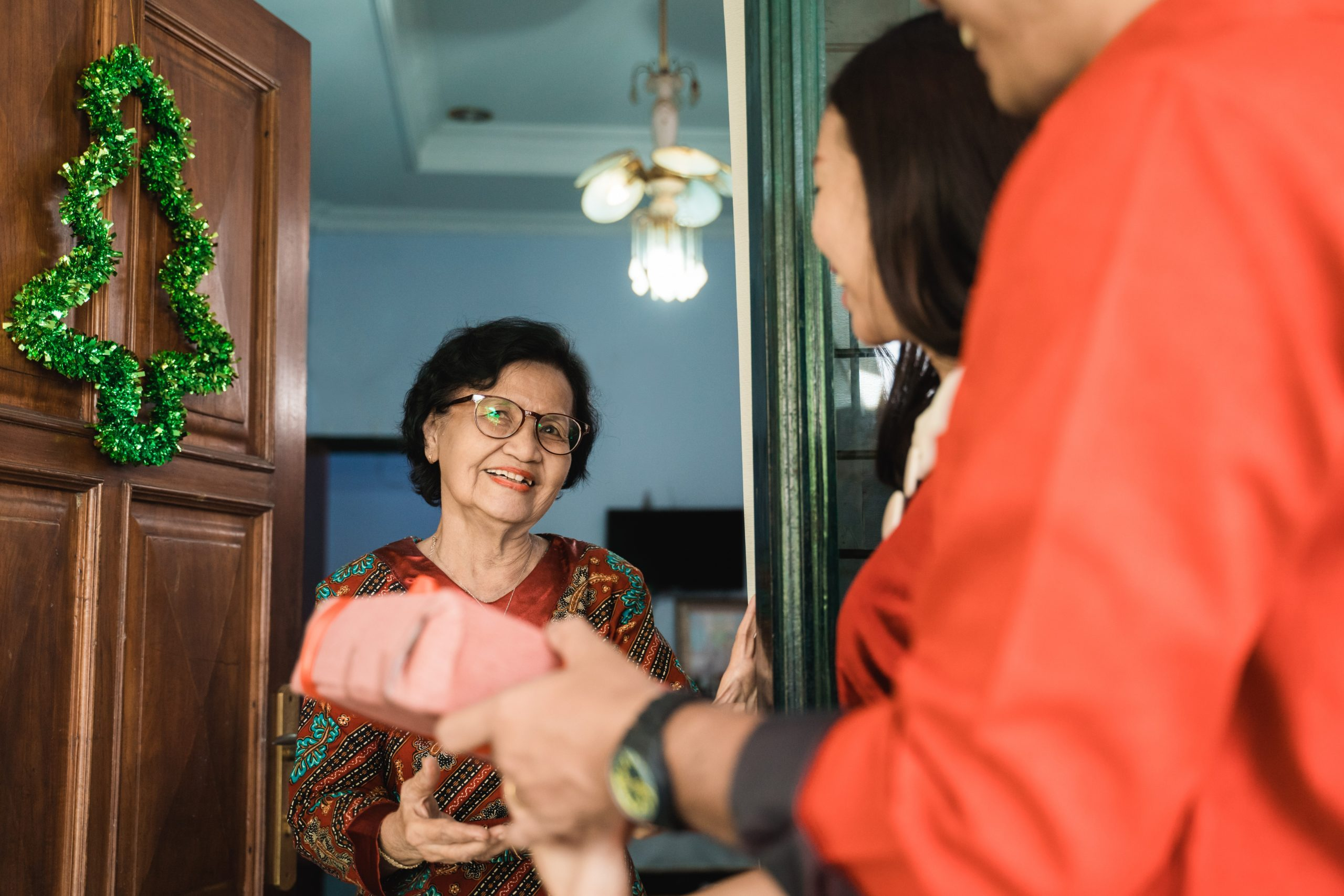 daughter giving surprise gift to senior mother. visiting family