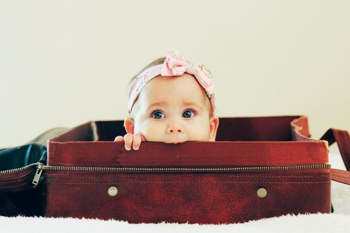 Portrait of adorable baby lying in vintage bag