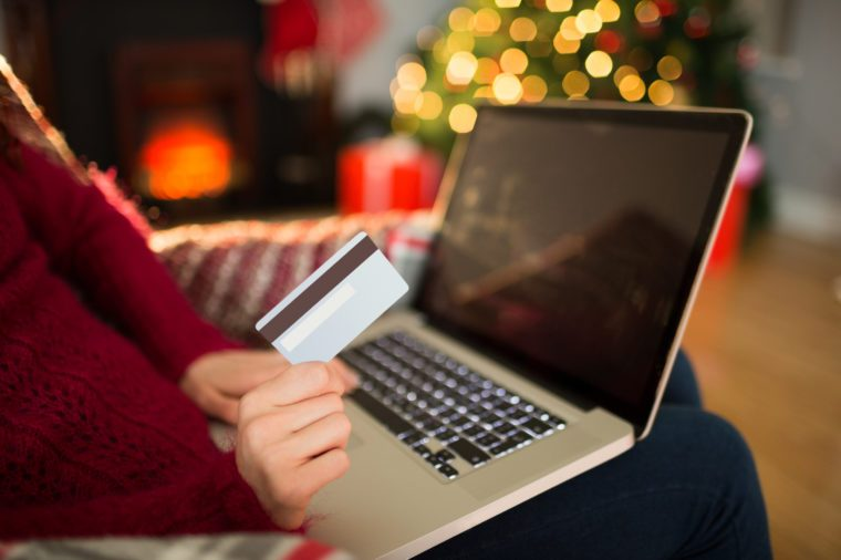 Woman shopping online with laptop at christmas at home in the living room