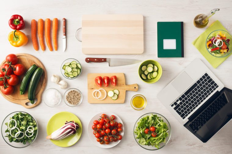 Vegetarian creative cooking at home with kitchen utensils, food ingredients and fresh vegetables on a wooden table, top view