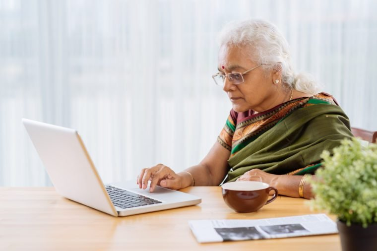 Mature Indian woman using laptop at home