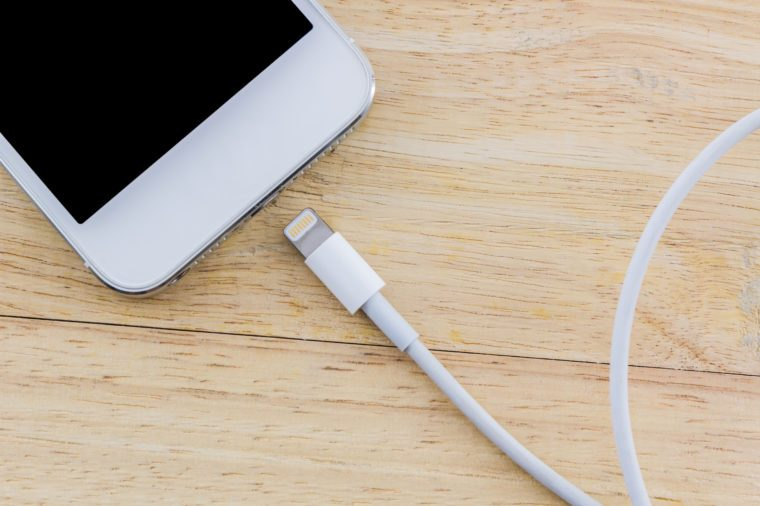 USB cable for smartphone on wood background.
