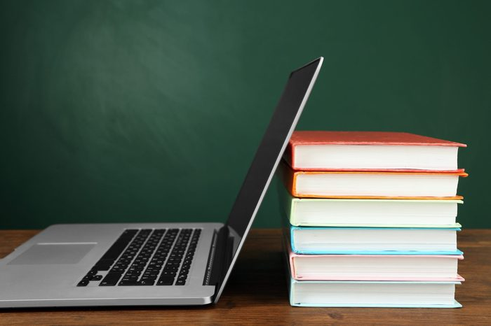Stack of books with laptop on table in classroom