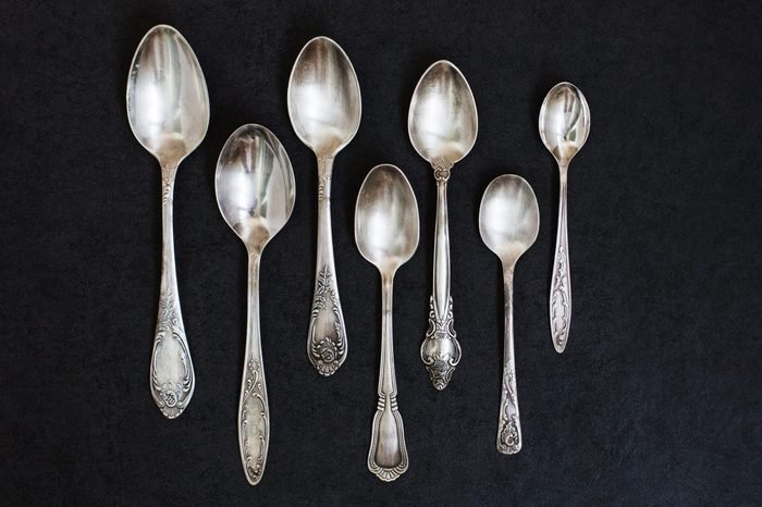 Silver spoons on the grey stone background.
