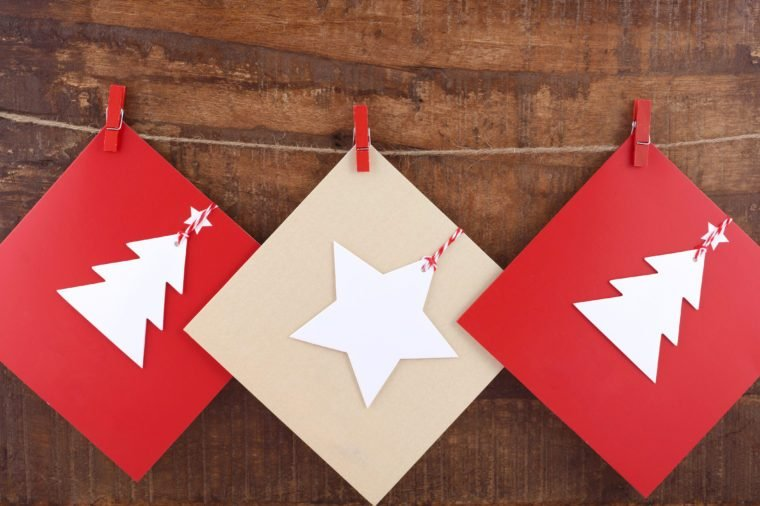 Handmade Christmas greeting card using cutout shapes on natural kraft paper hanging from pegs on string line.