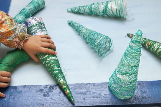 a horizontal frontal view of the hands of a little girl creating thread christmas tree