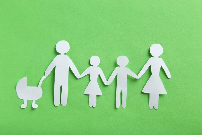 Happy paper family on green background