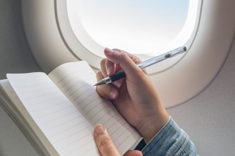 Woman writing on blank notebook while travelling on airplane.