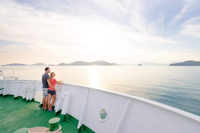 Romantic vacation. Young loving couple enjoying sunset on cruise ship deck. Sailing the sea.