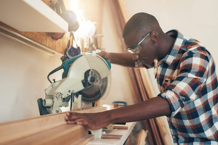 African artisan working with a chop saw in woodwork workshop