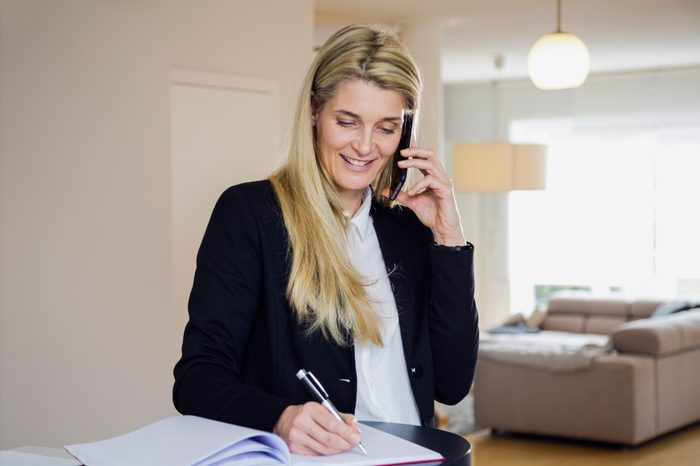 Attractive blonde middle-aged business woman using her phone and making notes. Casual business situation from person working at home. Modern looking living room in the background.