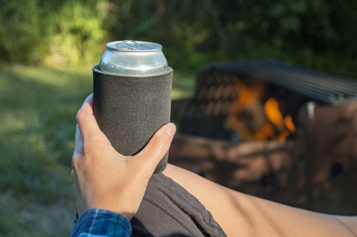 Woman holding a can of beer in a sleeve by the fire while camping