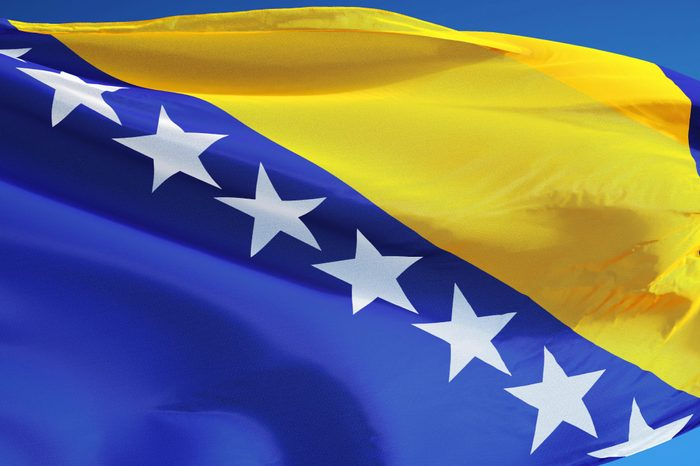 Bosnia and Herzegovina flag waving against clean blue sky, isolated with clipping mask alpha channel transparency