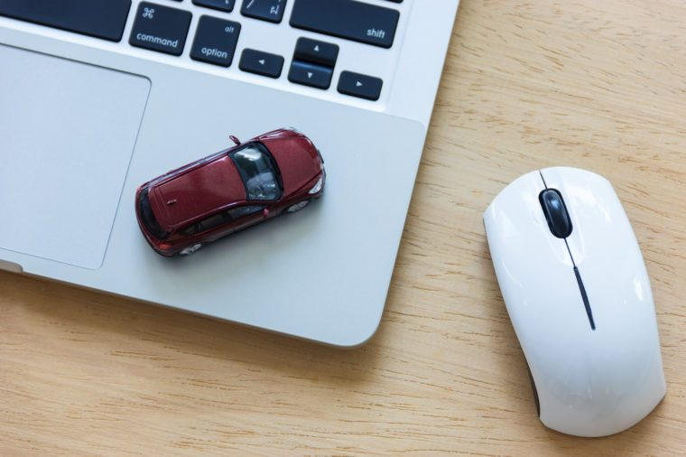 Car model on notebook and mouse on wooden desk. About car business concept such as transportation, rental, sell and buy
