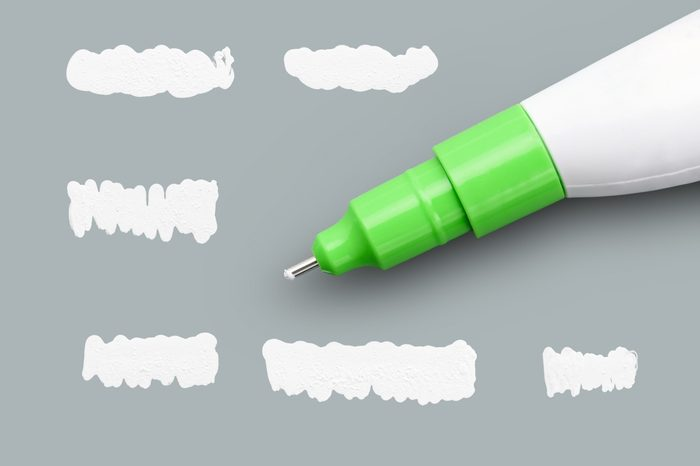 Correction pen and set of dried white fluid isolated on grey background. Mainly used to correct typewriting in the past or now mostly cover hand writing mistakes. With clipping path already included.