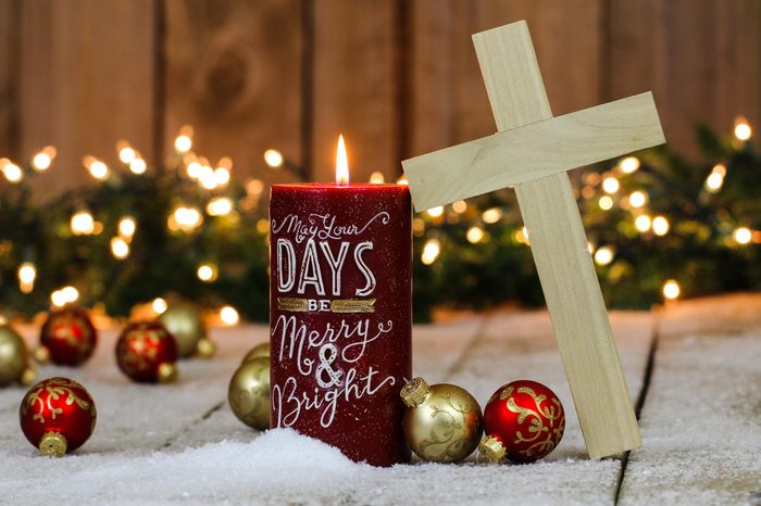 Christmas background with red candle, wood cross, red and gold ornaments and string of holiday lights with green garland border in snow; Christmas religious background