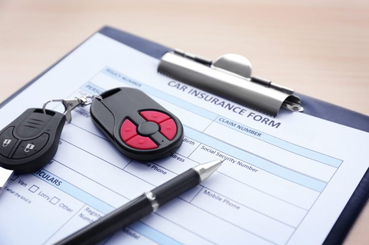 Car insurance form, pen and key on wooden table, close up view