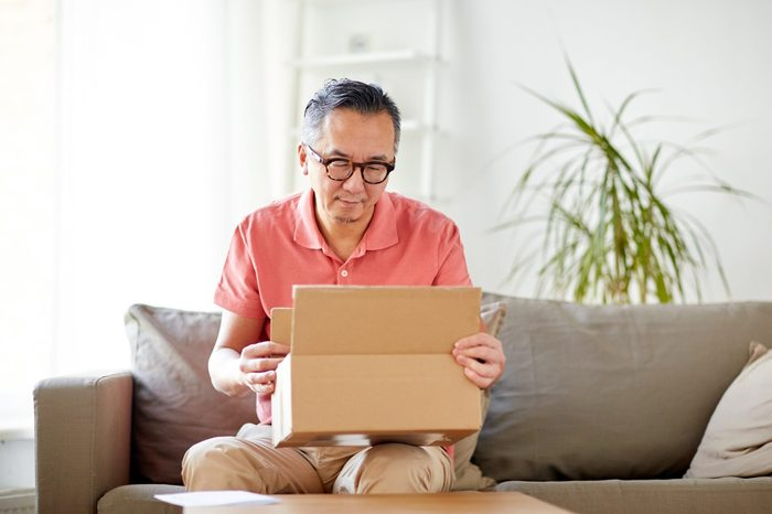 delivery, mail, consumerism and people concept - man opening parcel box at home