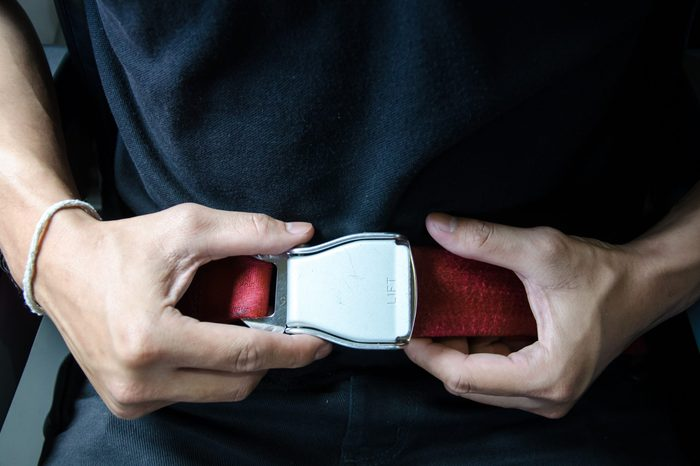 Hand of asian man unfasten seatbelt .
