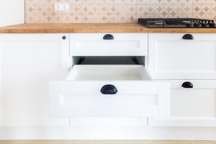 Opened kitchen drawer, kitchen in a traditional style with wooden white facade, black handles and wooden countertop