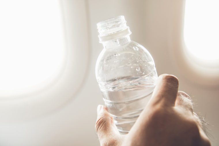 Passenger holding bottle of water about to drink preventing dehydration while traveling on the plane