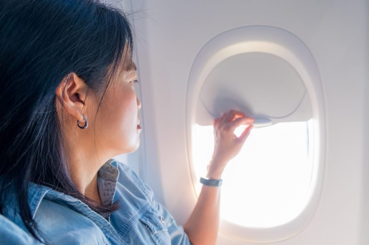 Asian Woman sitting at window seat in airplane and close the window when airplane take off,traveling concept