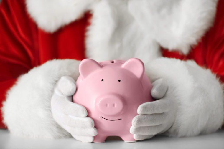 Santa Claus holding piggy bank at table