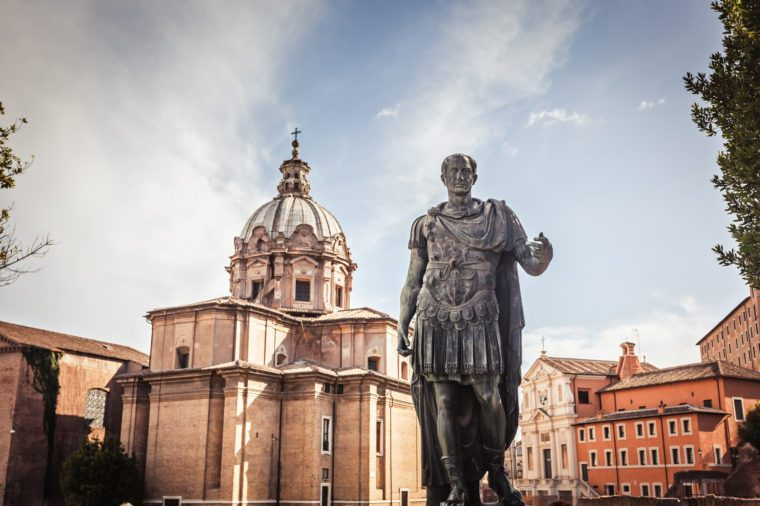 Julius Caesar statue with church of Saint Luca e Martina on the background - a bronze copy of the statue in the Capitol