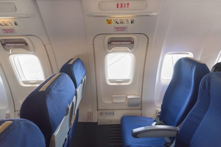 Empty aircraft seats close to emergency door exit
