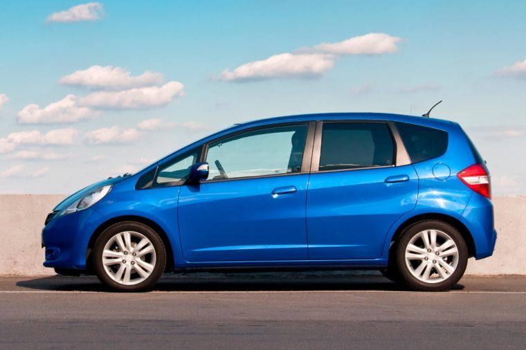 Blue car Honda Jazz parked on the road against the background of the sunny sky. Automotive photography.