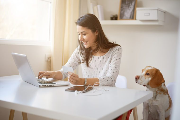 Young Caucasian businesswoman using credit card for on line payment. her dog next to her