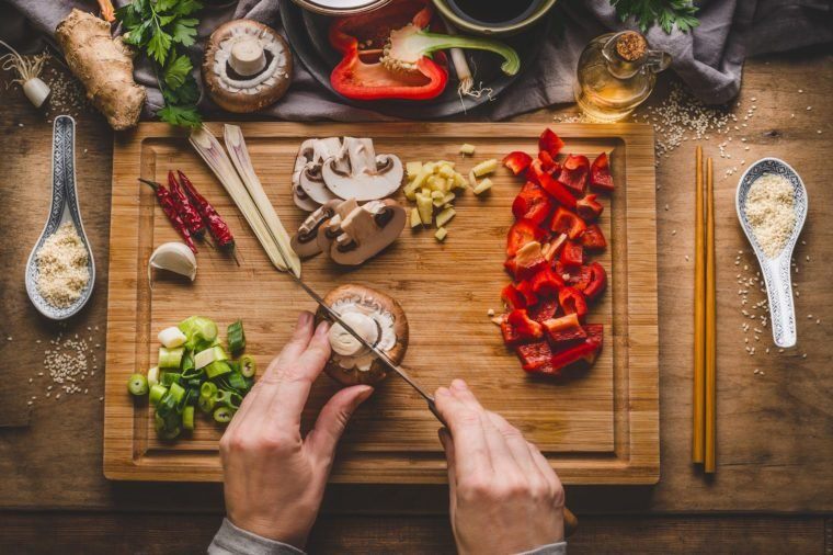 Vegetarian stir fry cooking preparation. Women female hands cut vegetables for stir fry on kitchen table background with ingredients, top view. Asian food , Chinese or Thai cuisine concept