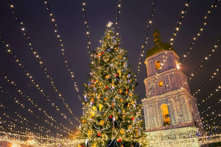 Christmas tree with lights outdoors at night in Kiev. Sophia Cathedral on background. New Year Celebration