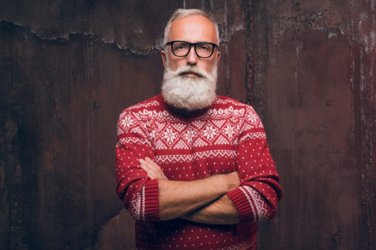 Beautiful senior man bearded in Christmas sweater. Santa Claus wishes Merry Christmas