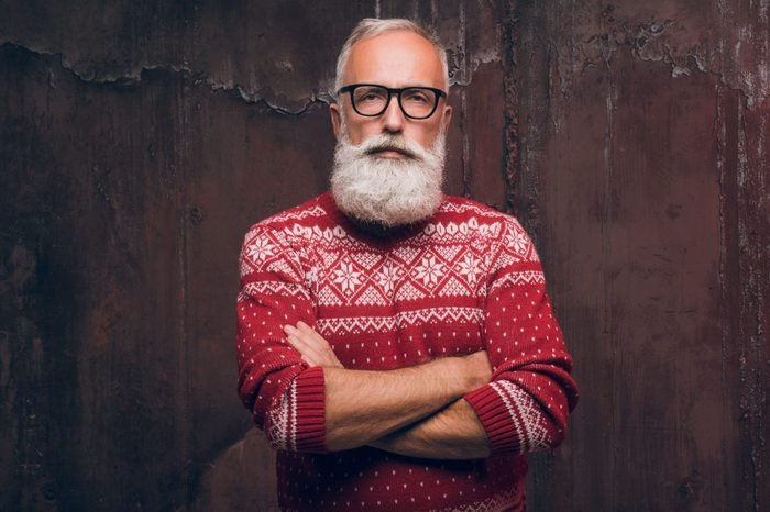 Beautiful senior man bearded in Christmas sweater. Santa Claus wishes Merry Christmas