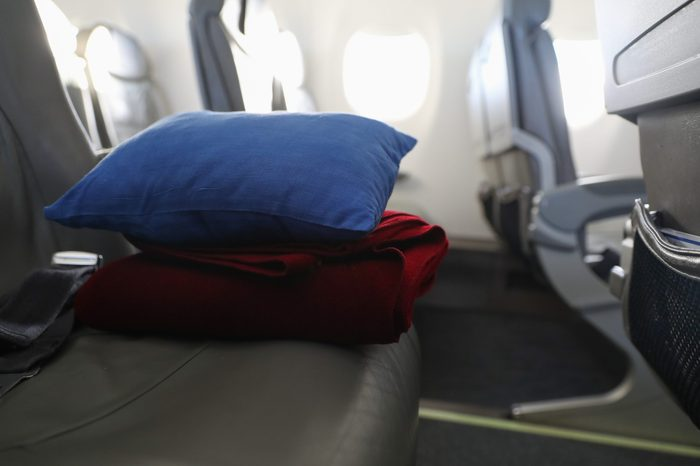 Pillow and blanket lying on the seat in the plane