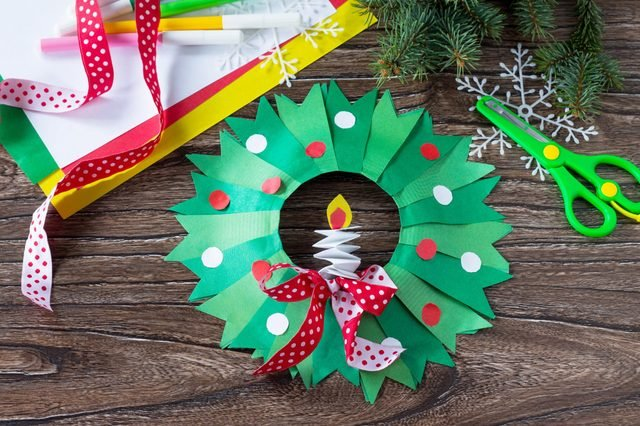 Christmas wreath with a candle on a written wooden table. Made by own hands. Children's art project for children. Craft for kids.