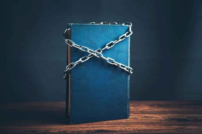 single blue book standing up on wood table with chains crossed across the cover