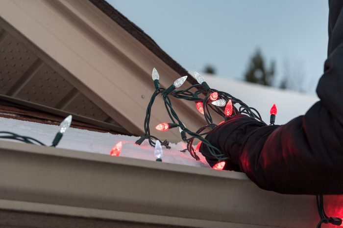 Close up of arms hanging a tangled pile of red and white Christmas lights on a snow covered roof.