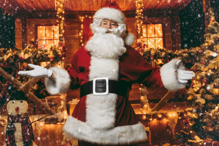 Portrait of surprised Santa Claus in the courtyard of his house decorated with Christmas lights. Christmas and New Year concept.