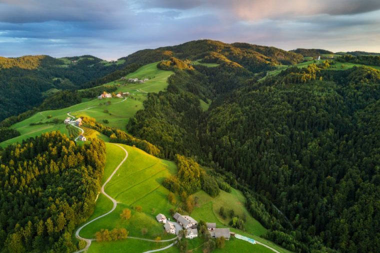 Aerial shot of green hills of Slovenia at sunrise