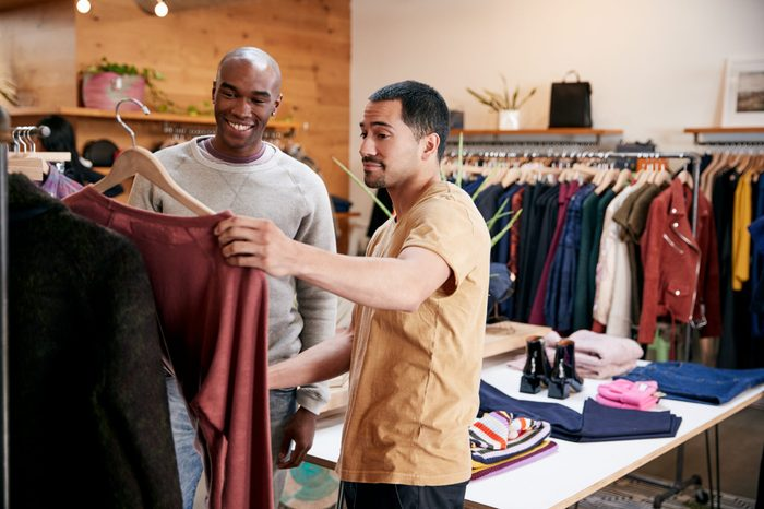 Two male friends looking at clothes in a clothes shop