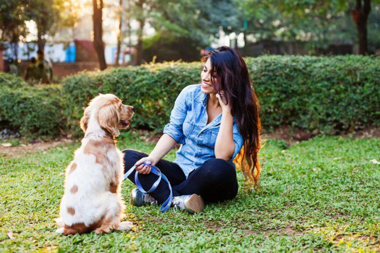 Beautiful indian girl training her cocker spaniel dog