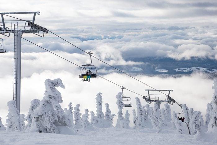 Ski or snowboard on chairlift at Big White Resort, Kelowna, British Columbia, Canada