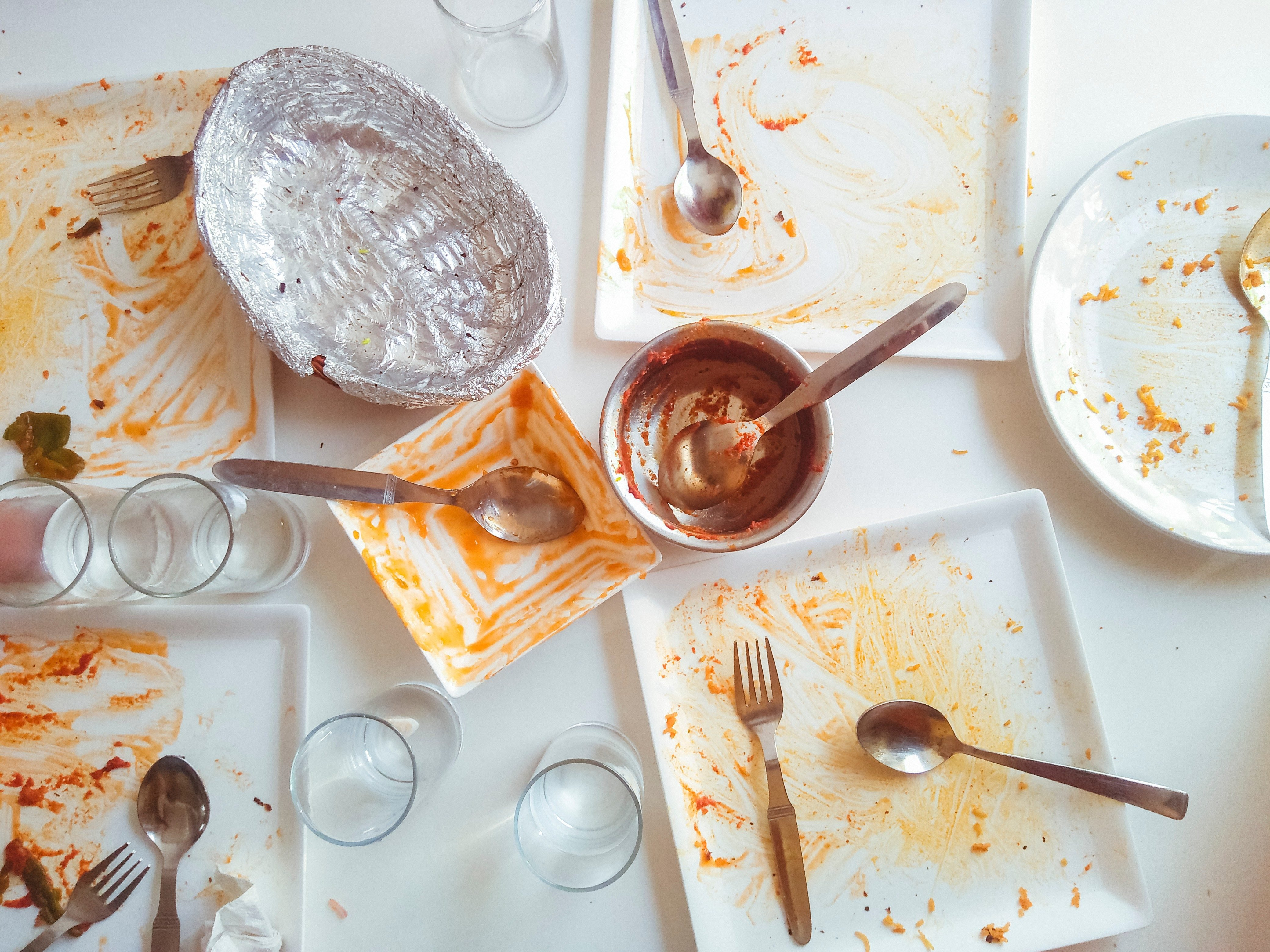 Messy dining table and crockery after lunch by many people. No people, still life, table top image shot from top angle in natural light in a restaurant.