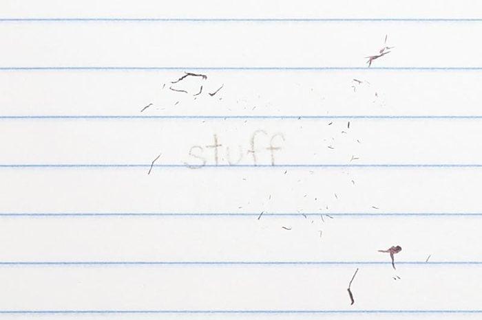 "erased text ""stuff"" with eraser shavings on loose leaf paper"
