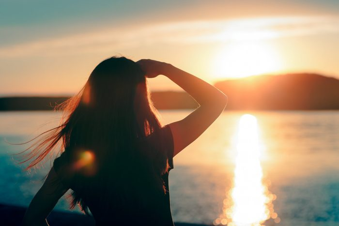 Happy Hopeful Woman Looking at the Sunset by the Sea. Silhouette of a dreamer girl looking hopeful at the horizon